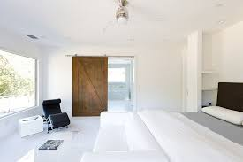 bedrooms white minimalist bedroom with barn door and white bed