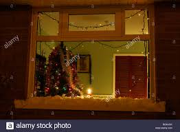 candle burning in the window of a house with tree in the