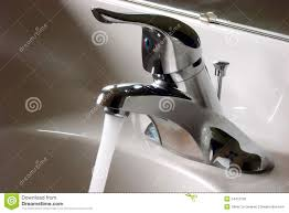 bathroom faucet open and running with water flow royalty free