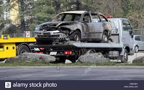 wrecked car fire damage on wrecked car loaded on a flatbed tow truck at the