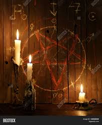 the background of halloween three burning candles against the background of wooden planks with