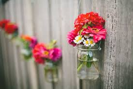 hanging jar flowers on outdoor backyard wooden fence for