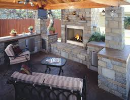 extraordinary stone outdoor kitchen featuring outdoor fireplace