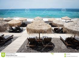 Beach Lounge Chair Umbrella Lounge Chairs With Umbrellas On The Empty White Beach Santorini