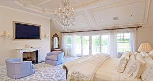 master bedroom with fireplace and neutral walls and wall sconces