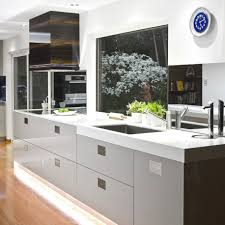 contemporary kitchen design with sleek white countertop and simple contemporary kitchen design with sleek white countertop and simple sink with wooden floor and window image