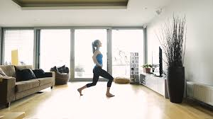 active young woman working out at home in her living room doing