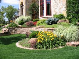 beautiful cobblestone siding sloped landscaping and wrought iron