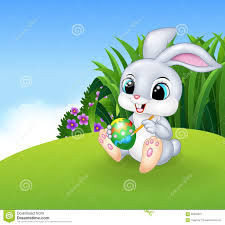 cute easter bunny painting an egg on the meadow background stock