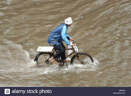 bicycle raincoat man in raincoat on bicycle on record monsoon heavy rainfall day in