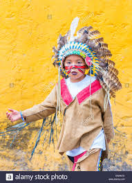 native american boy with traditional costume participates at the