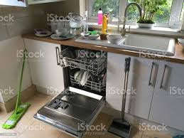how to clean soiled kitchen cabinets image of kitchen with loaded dishwasher open washing up needing cleaning of dishes plates knives forks and saucepan ready for washing up