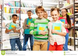 children in library hold exercise books and stand stock photo