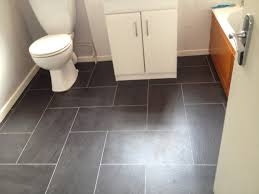 grey ceramic flooring tile with white vanity also toilet bathtub