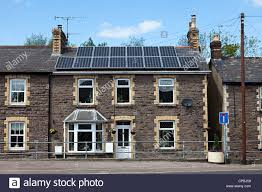 old stone house in terrace with modern solar panels on roof stock