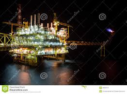 the large offshore oil rig drilling platform at night stock