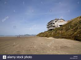 a beach house sits on eroded sand dunes by pacific ocean waves and