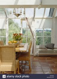 terracotta tiled floor in conservatory dining room with wicker