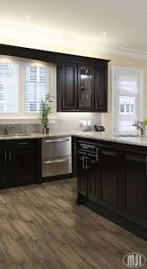 stone countertops dark kitchen cabinets with light lighting