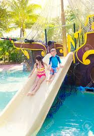 kids playing on a water slide at a waterpark stock photo picture