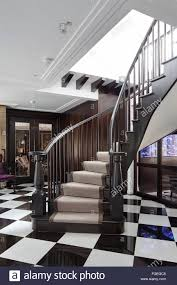 curved wooden staircase with black u0026 white tiled floor in hallway