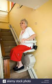 old woman using a chair lift stock photo royalty free image