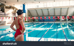 Inside Swimming Pool by Woman Professional Swimmer Wearing Red Swimsuit Stock Photo