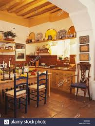 ladderback chairs at wooden table in spanish country kitchen with