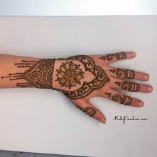henna design on the top of the hand with a floral mandala in the