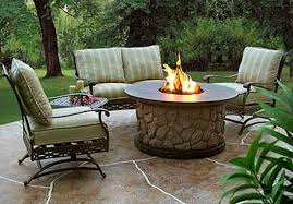 cozy patio with gas fire pit on stone barn table with striped