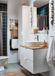 a small white bathroom with a high cabinet and a washstand