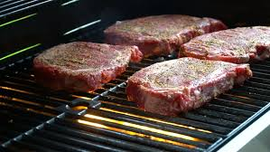 grillk che grilling bbq beef steak on gas bbq grill chef is cooking asian