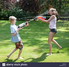 family playing with water guns in backyard stock photo royalty