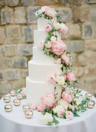 four tier round white and blush pink wedding cake with fresh