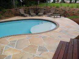 small pool with white concrete deck having concrete stair on green