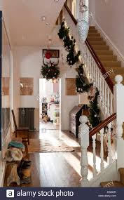 decorations hung from a staircase in a hallway with wooden