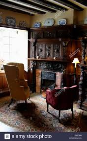 interior of an english country house next to a fireplace with two interior of an english country house next to a fireplace with two chairs and a reading lamp
