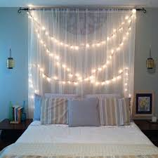 zen bedroom with sheer fabric and string lights as a headboard