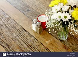 wooden table in coffee shop with flower arrangement and salt