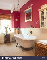 rolltop bath in dark pink bathroom with cream tongue groove