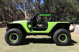 4 door jeep wrangler jacked up behind the wheel of the 707 hp jeep trailcat concept