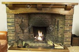 ancient open log fireplace with wrought iron fire irons and oak