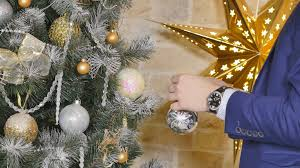 close up of man hanging decorative toy ball on christmas tree