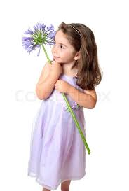 pretty young in a dress holding a large purple agapanthus