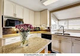images of white kitchen cabinets with black appliances kitchen island with granite top and flowers