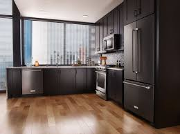 black glass backsplash kitchen black kitchen appliances white cabinets grey blue herringbone