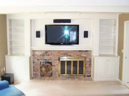 brown brick wall fireplace with television above on the white wall