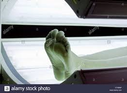 Lit Bed Up Bare Feet And Legs In Lit Tanning Bed Stock Photo Royalty Free
