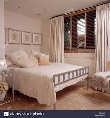 cream metal bed frame cream cushions and cover on simple metal bed in modern bedroom