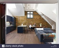 open plan kitchen and living area with skylights and exposed brick